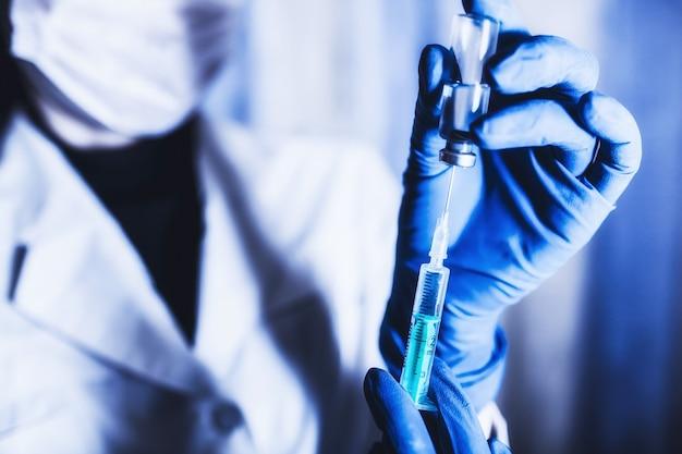注射器と手のクローズアップ。注射器に薬を充填するワクチン接種の概念。医師の経歴