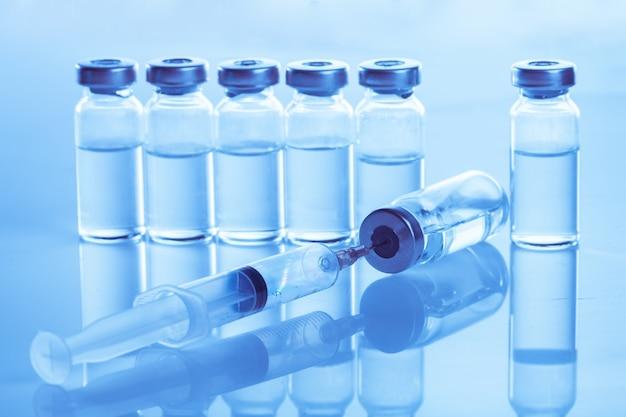 青い背景の注射器と医療アンプル