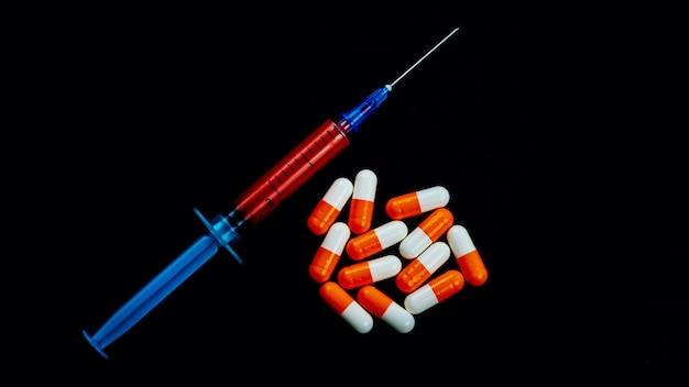 黒の孤立した背景に注射器と錠剤。コロナウイルスのパンデミックの概念。