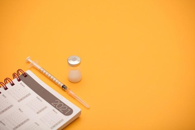 Шприц и канистра с вакциной, с календарем на 2021 год, оранжевый фон