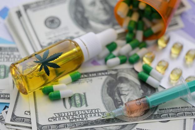 Syringe bottle of marijuana pills lie against