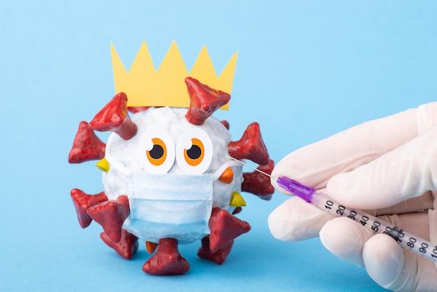 남자의 손에 주사기가 마스크와 왕관이있는 바이러스의 양식화 된 모델에 주사를합니다.