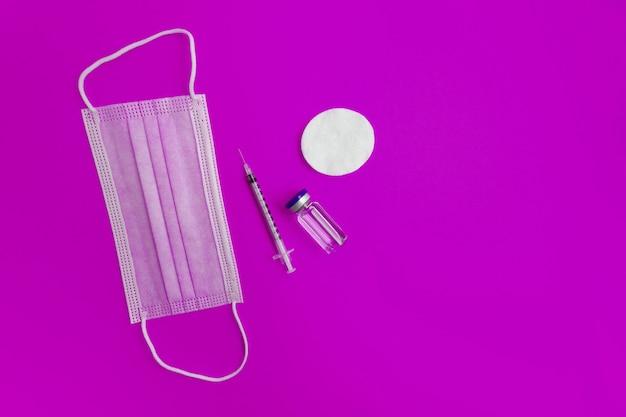 주사기, 의료 마스크, 분홍색 배경에 약이 든 앰플