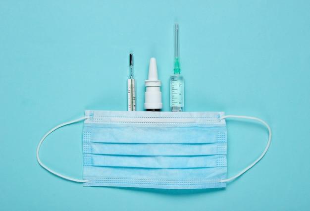 주사기, 의료 마스크, 온도계, 파란색 종이에 비강 스프레이