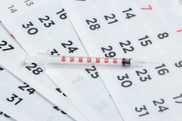 Шприц на ежемесячном календаре крупным планом. вакцинация