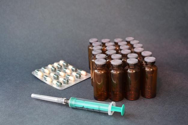 Шприц, таблетки и флаконы на сером фоне. фото изображение.
