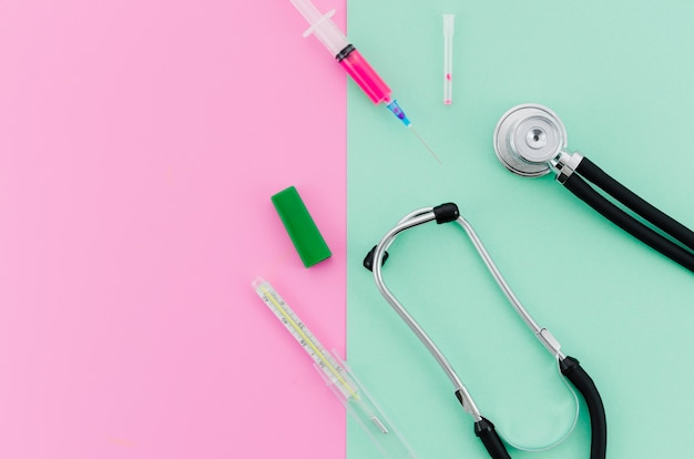 Syringe; stethoscope; thermometer on pink and mint green background