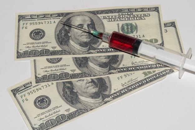Шприц с кровью на белом фоне с деньгами