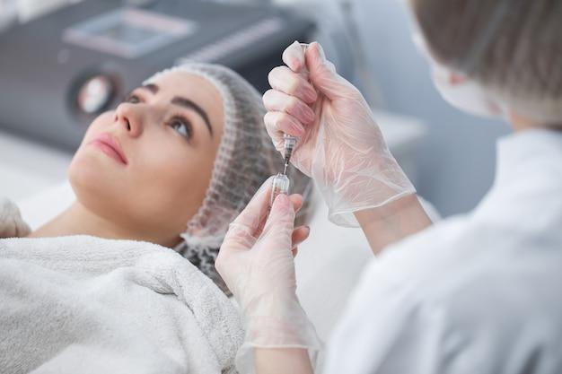 顔の輪郭や増強のためのフィラー付きシリンジ。モデル、視点。美容クリニック。ヘルスケア、美容、クリニック
