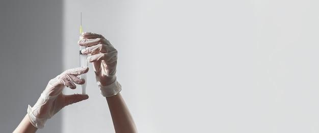 Шприц с иглой в руках медсестры на белом фоне копией пространства для текста медицинского баннера