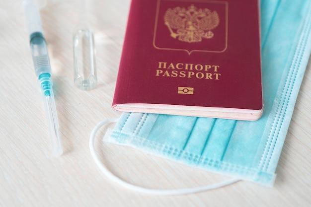 Шприц с иглой, флаконом, хирургической маской и российским паспортом на белом столе, готовом к использованию. фон вакцины против covid или коронавируса, паспорт иммунитета к covid-19
