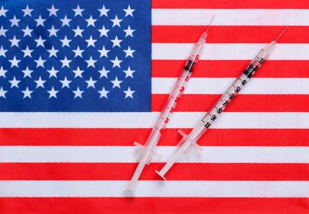 아메리카 합중국의 국기와 주사기. 백신 접종