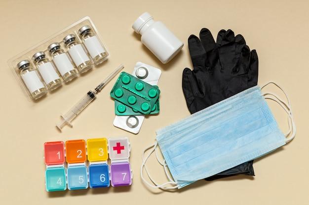 泡の手袋のマスクの錠剤とベージュの背景の丸薬のためのボクシングのワクチンと注射器