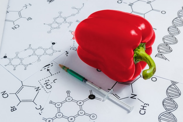 Syringeand red pepper on white background with chemical formula