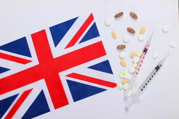 대 브리튼의 국기와 주사기와 약. 백신 접종. 유행성 코로나 19