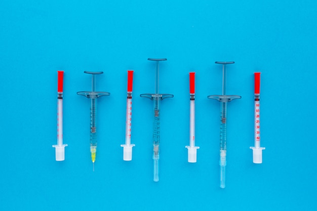 Syringes organized in a row over blue