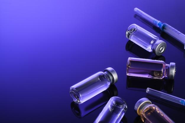 주사기, 작은 병, 백신 유리 병, 진한 파란색 배경에 약. 코로 노 바이러스 백신 접종, 백신 임상 시험, 의료 연구