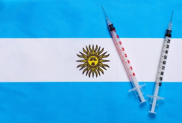 아르헨티나의 국기와 주사기. 백신 접종. 유행성 코로나 19