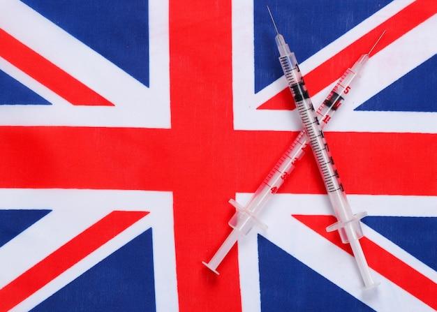 대 브리튼의 국기와 주사기. 백신 접종. 유행성 코로나 19
