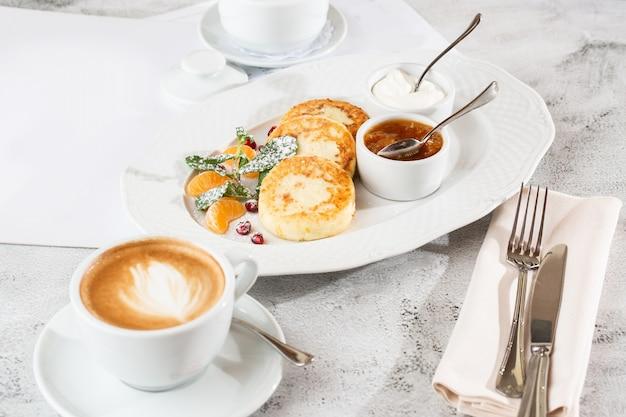 カッテージチーズのパンケーキ、syrnikiまたはチーズケーキ、クリーム、蜂蜜、ミントの白い繊維のテーブルに分離されました。手作りの料理。おいしい朝食。セレクティブフォーカス。 hotizontalの写真。