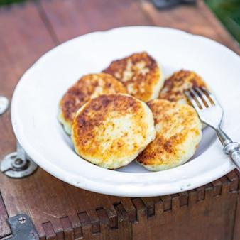 シルニキの甘いパンケーキカッテージチーズの朝食屋外の食事の軽食テーブルのコピー宇宙食