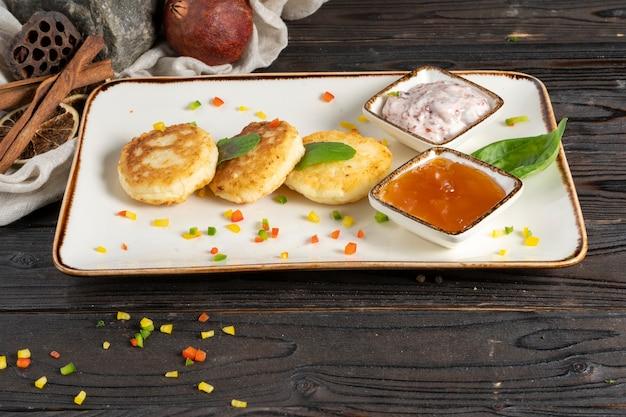 シルニキ-カッテージチーズ、卵、小麦粉をセラミックプレートにジャムとヨーグルトベリーソースで作った伝統的なロシアのパンケーキ