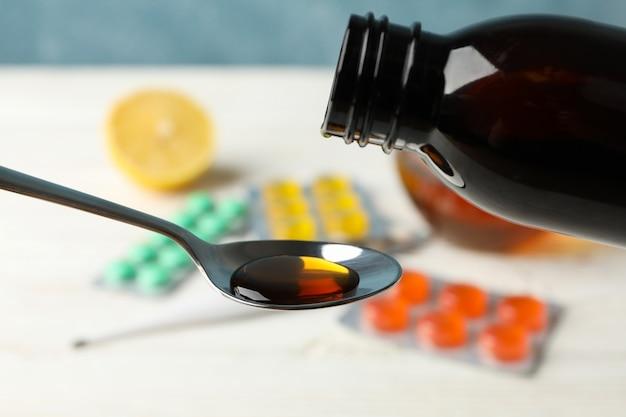 錠剤のスプーンに注ぐシロップ、クローズアップ