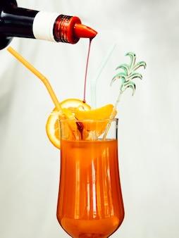 Сироп наливая в тропический коктейль