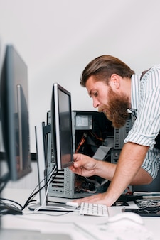 System administrator turn on computer monitor in office. bearded programmer plug in electronic equipment for work. business, programming, workplace concept