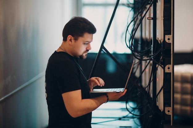 Системный администратор работает с ноутбуком.