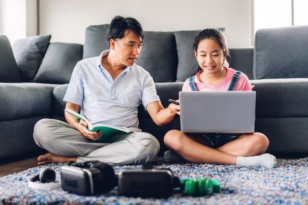 Отец и азиатская маленькая девочка малыша изучая и смотря портативный компьютер делая домашнюю работу изучая знания с он-лайн обучением system.children видео-конференция с репетитором учителя на дому