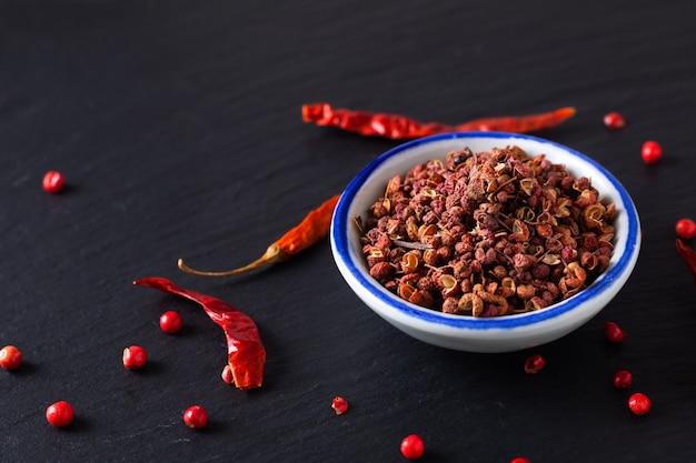 Szechuan, szechwan pepper in small ceramic bowl on black slate stone board