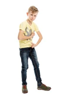 ジーンズと黄色のtシャツで10代の少年に立って筋肉を示しています。白い背景に分離された完全な高さ。