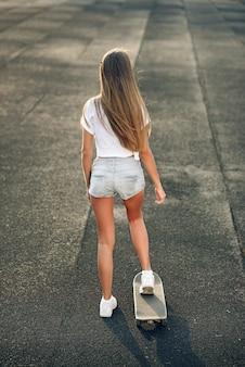 白いtシャツ、ショートパンツ、スニーカーでかわいい美しい若い10代女性がスケートボードに乗る