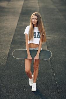 白いtシャツ、ショートパンツ、スニーカーの手でスケートボードに立っているかわいい美しい若い10代女性