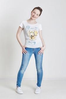 ジーンズとtシャツのポーズモデルの10代の女の子