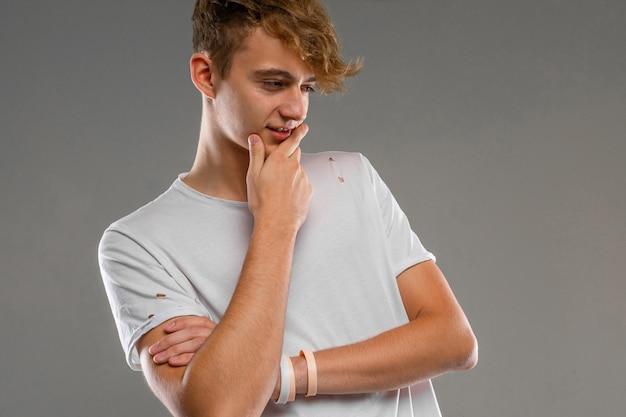 夢のような表情で灰色のtシャツを着た男の灰色、クローズアップに対してスタジオでポーズをとってハンサムな感情的な10代の少年