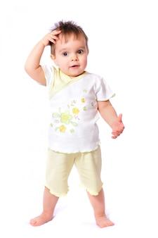 白いtシャツと黄色のショートパンツで幸せな1歳の赤ちゃん女の子
