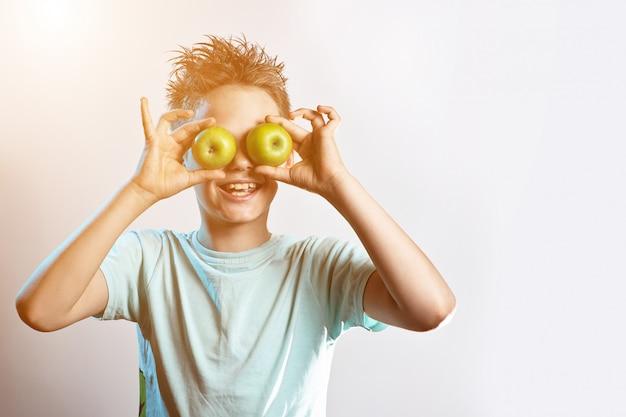 青いtシャツを着た少年が2つの緑のリンゴを目に入れて笑う