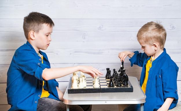 黄色のtシャツとデニムジャケット、シャツの2人の美しい男の子の肖像画。男の子は白い木製の背景でチェスをしています。リトルブラザーズはチェスをしています。