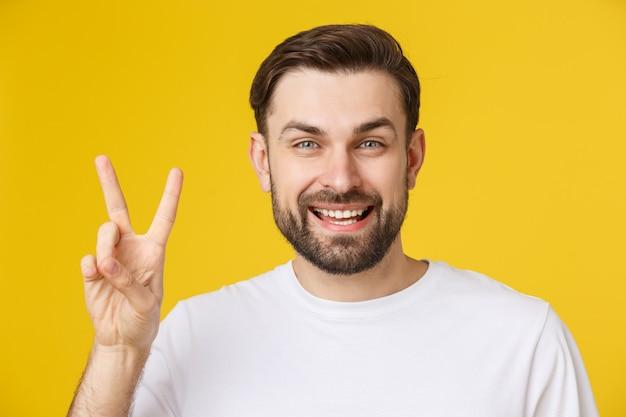 勝利のサインを行う指を示す笑みを浮かべてストライプtシャツを着ている若いハンサムな男。ナンバー2