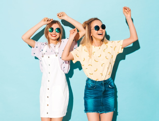 トレンディな夏のカラフルなtシャツの服の2人の若い美しい笑顔金髪流行に敏感な女の子。