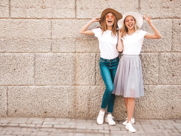 トレンディな夏の白いtシャツ服で流行に敏感な女の子を笑顔2つの若い美しいブロンドの肖像画。