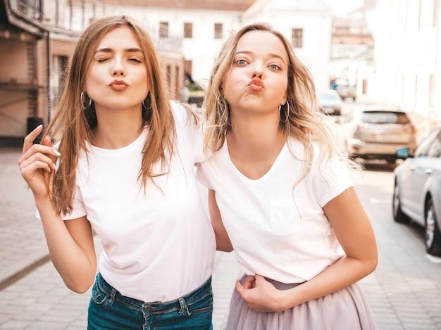 トレンディな夏の白いtシャツ服で流行に敏感な女の子を笑顔2つの若い美しいブロンドの肖像画。 。ポジティブモデルはアヒルの顔になります