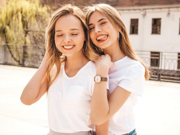 トレンディな夏の白いtシャツ服で流行に敏感な女の子を笑顔2つの若い美しいブロンドの肖像画。 。楽しいポジティブなモデル