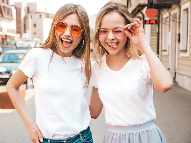 トレンディな夏の白いtシャツ服で流行に敏感な女の子を笑顔2つの若い美しいブロンドの肖像画。 。サングラスを楽しんでいるポジティブなモデル。