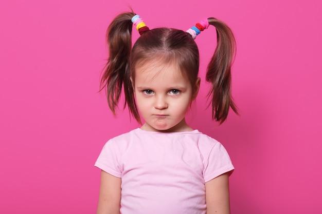 ピンクの壁に悲しい少女が立っています。かわいい子供はバラのtシャツを着ており、2つのファニーポニーテールにカラフルなシュシュがたくさんあり、ふわふわした唇で傷ついています。遊び場で動揺の子。