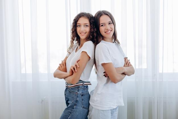 Tシャツを着た2人の女の子が背中合わせで立っています。