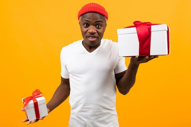 白いtシャツを着た笑顔でかわいい驚いた黒人アフリカ人が2つのボックスを保持しているバレンタインデーの黄色の赤いリボンが付いているギフト
