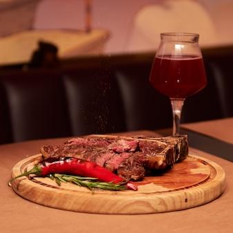 레스토랑에서 로즈마리 가지 후추 소금과 와인 한 잔을 곁들인 t 뼈 쇠고기 구이 스테이크 고기